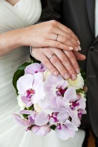 Brautpaar Hände auf Brautstrauß